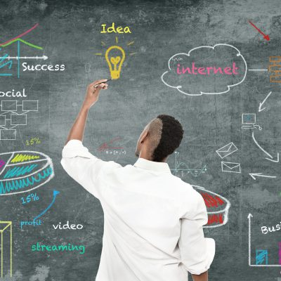 photo of afro amercian man drawing a strategy diagram on the wall